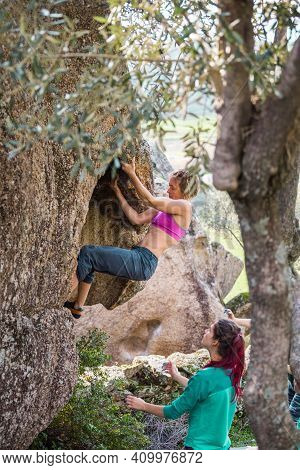 Friends Go In For Sports In Nature, Bouldering On Rocks, Girl Climbs A Big Stone, Woman Is Belayng P