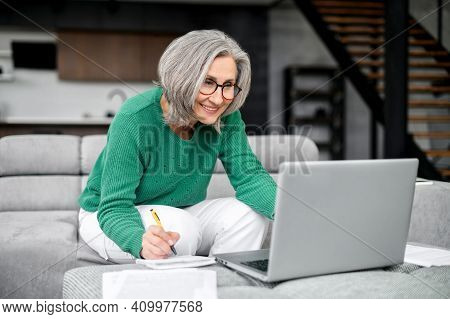 Well-dressed Gray Haired Woman On Retirement Managing Family Budget At Home, With Glasses, Watching