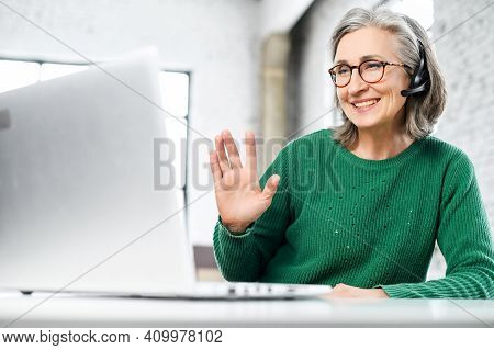 Cheerful Aged Woman With Headset, Has Wrinkles On The Face, Dressed In Green Warm Sweater, Smiling,