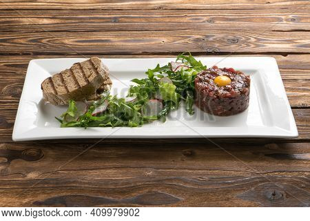Marinated Beef Tartare With Quail Egg Yolk, Lettuce, Radish And Grilled Ciabatta In A White Ceramic
