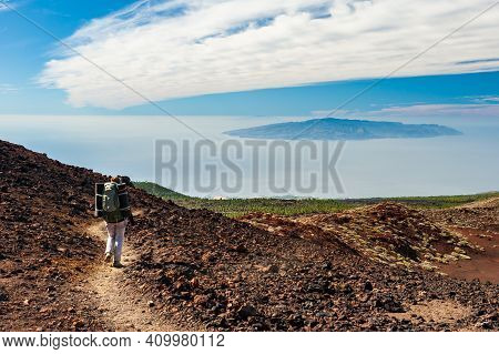 Canary Island La Gomera In Sea And Young Woman Hiker With Backpack Descending From Pico Del Teide Mo