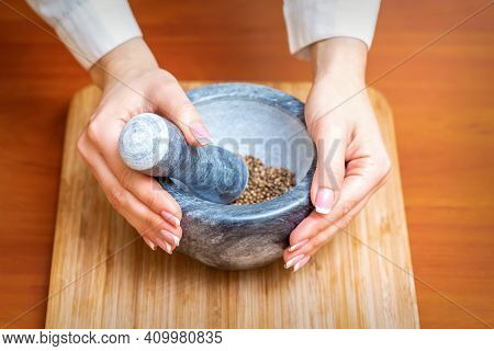 Female Hands Grind Dry Pepper Spices In Mortar On A Wooden Kitchen Board
