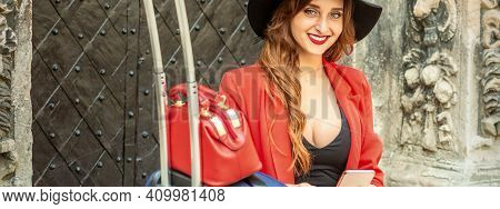 Portrait Of A Beautiful Young Caucasian Traveling Woman Sitting At The Door With Suitcase And Smartp