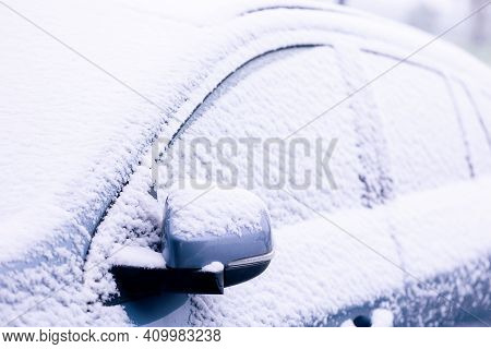 A Portrait Of The Side Windows And The Wing Mirror Of A Car Getting Completely Snowed Under During A