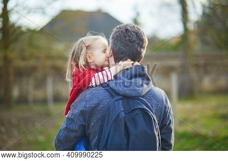 Man Holding Adorable Toddler Girl In His Arms During A Walk. Happy Smiling Daughter Hugging And Kiss