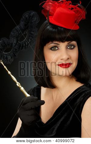 Studio portrait of young woman in red hat holding mask looking at camera, smiling.