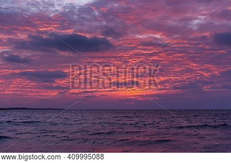 Pink Sunset On The Sea. Bright Juicy Landscape With Low Cumulus Clouds On The Horizon. Purple, Lilac