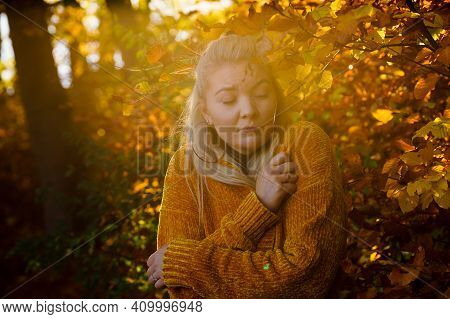 Woman In Autumn Park Trembling And Feeling Cold After Walk During Frosty Weather, Huggs Herself To W