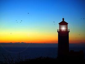 Lighthouse With Lens Flare On The Washington Coast At Sunset