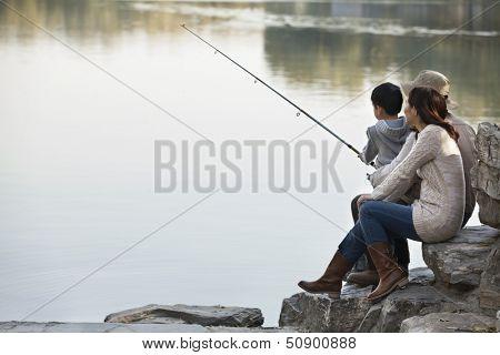 Family fishing off of rocks at lake
