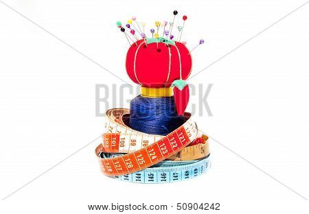 Three Tape Measures Coiled Around Roll Of Cotton And Pin Cushion