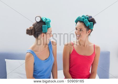 Girls wearing hair rollers sitting in bed at sleepover
