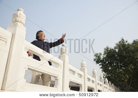Senior man practicing Taijiquan in Beijing, arms in front