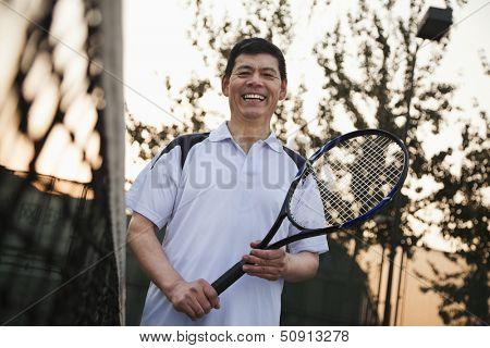 Senior men playing tennis, portrait