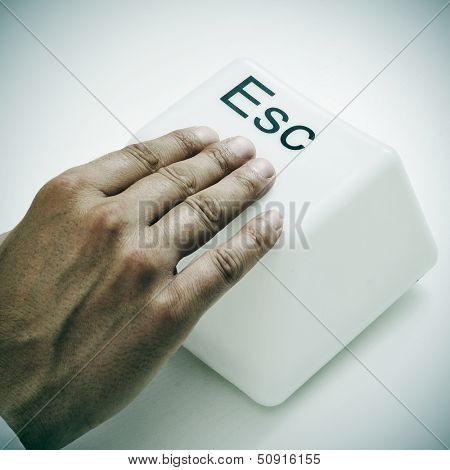 a man pressing a giant escape key with his hand