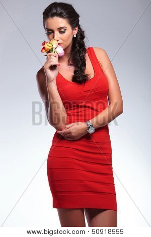 young beauty woman smelling flowers with her eyes closed. on gray background