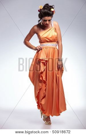 full length photo of a young fashion woman looking down in front of her while holding her dress with one hand. on gray background