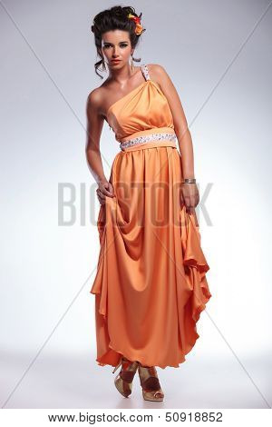 full length photo of a young fashion woman holding both hands on her dress and looking into the camera. on gray background