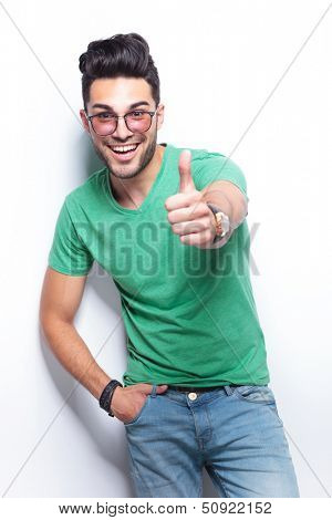 young casual man showing the thumb up gesture to the camera with a smile on his face. on white background poster