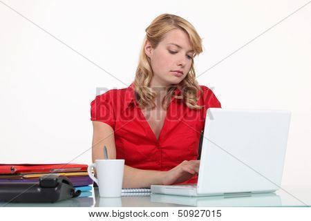 Bored secretary typing on her laptop