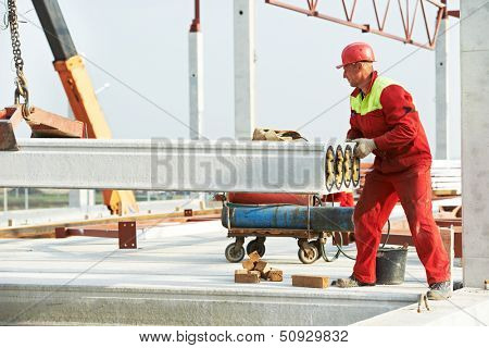 builder worker in safety protective equipment installing concrete floor slab panel at building construction site poster