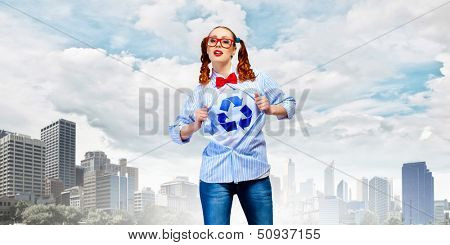 Young woman acting like super hero with recycle sign on chest poster