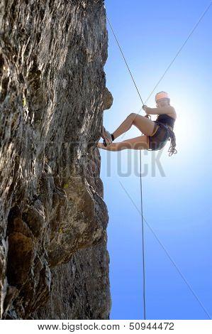 Full length of young woman climbing rock