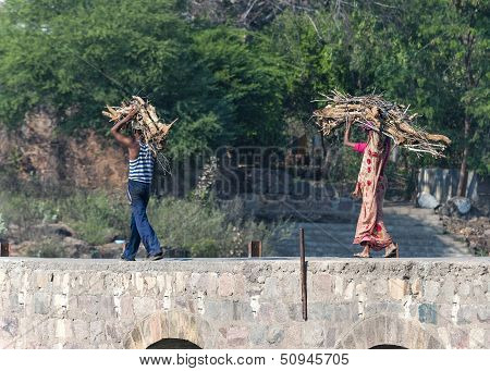 Couple, Man And Woman In Sari, Carry Firewood On Head Over Bridge.