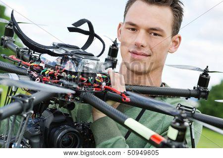 Closeup portrait of male engineer holding UAV octocopter in park