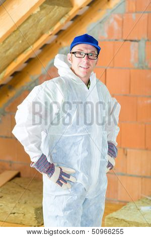 Worker in overall doing construction the roof with thermal insulating material