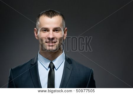 Front view of self-confident man in dark suit with black tie. Concept of professionalism and success in business