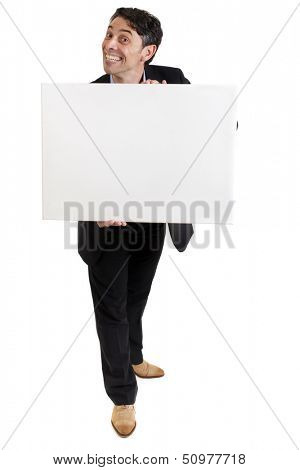 Smart, middle-aged businessman with a cheesy insincere toothy grin holding a blank white sign in his hands with copyspace for your text or advertisement, isolated on white