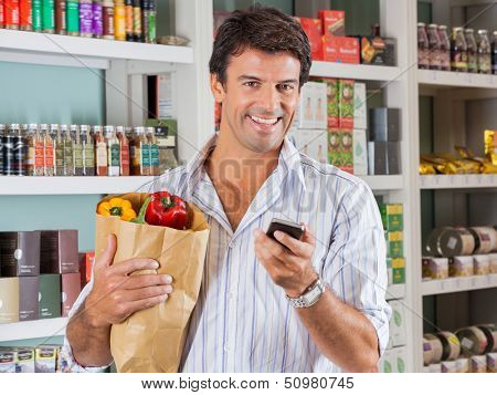 Portrait of happy male customer with mobile phone and grocery paper bag in store