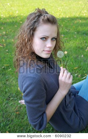 Girl Holds A Dandelion In The Hand