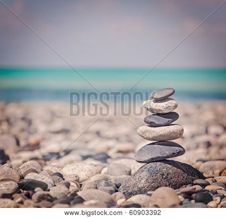 Vintage retro hipster style travel image of Zen meditation background -  balanced stones stack close up on sea beach poster