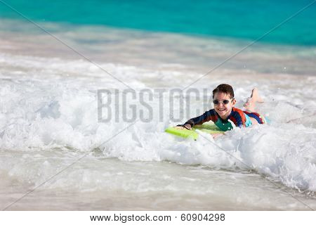 Little boy on vacation having fun swimming on boogie board poster