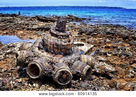 Military hardware and vehicle parts discarded by US forces at Million Dollar Point Vanuatu after WW2. Aero engine in foreground. poster