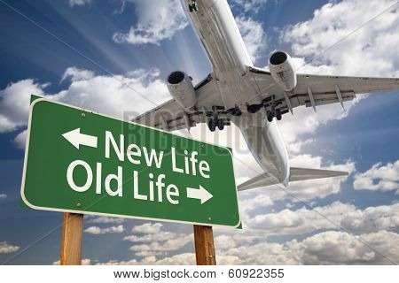 New Life, Old Life Green Road Sign and Airplane Above with Dramatic Blue Sky and Clouds.