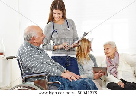 Caregiver doing survey with senior citizens in a nursing home