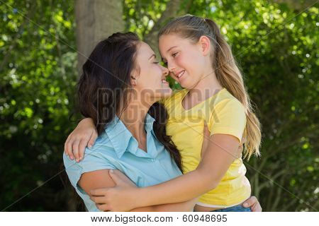 Smiling mother and daughter rubbing noses in park