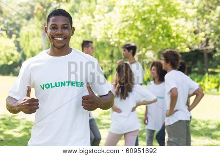 Portrait of smiling volunteer showing thumbs up with friends disucssing in background