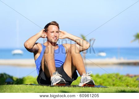 Man exercising sit-ups outside. Male fitness model training situps exercise outdoor in summer during workout. Handsome fit muscular sport model.