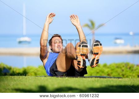 Fitness man doing sit-ups exercise for abs outdoors. Fit male athlete cross training jackknife sit up during workout. Muscular handsome young caucasian man working out outside.
