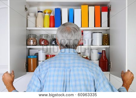 Closeup of a mature male looking into his pantry, The cupboard is full of groceries. The man is seen from behind and is unrecognizable.