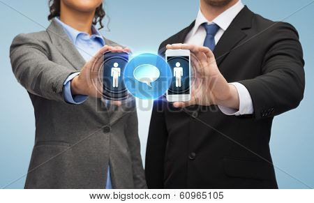 business, technology and internetconcept - businessman and businesswoman with social or business network on smartphone screens
