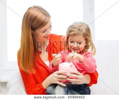 family, children, money, investmen and happy people concept - happy mother and daughter with small pink piggy bank