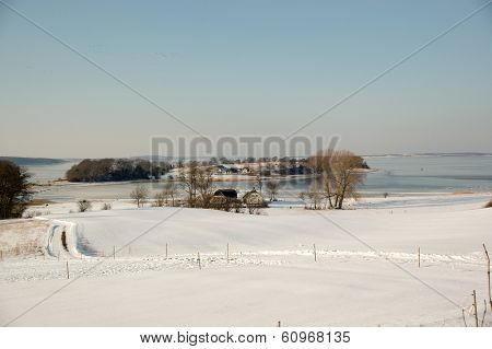 Idylic winter landscape with, fram, fields and frozen sea.
