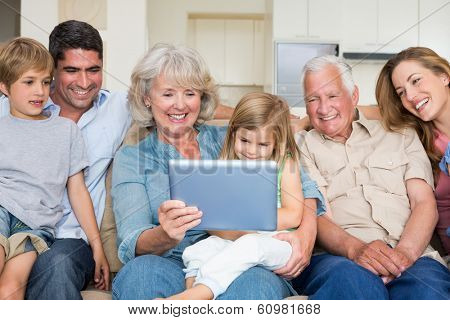 Happy multigeneration family using digital tablet at home
