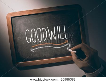 Hand writing the word goodwill on black chalkboard