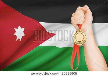Medal In Hand With Flag On Background - Hashemite Kingdom Of Jordan